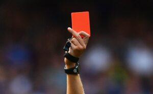 レッドカードを持つ審判の手