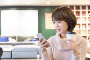カフェでコーヒを飲みながらスマホを触る女性