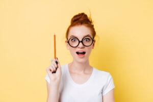 鉛筆を持って驚くメガネ女子